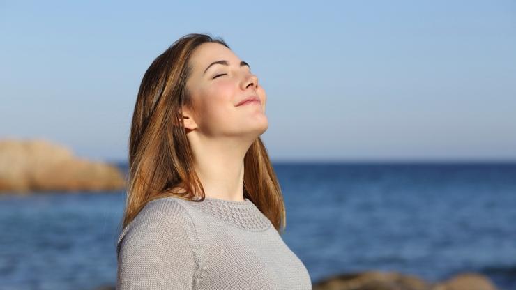 Happy woman breathing deep fresh air on the beach